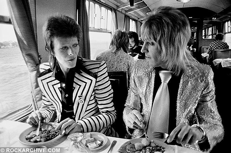 David Bowie and Mick Ronson eating lunch on a train to Aberdeen in 1973, heading for the first gig of Bowie's final Ziggy tour. © Mick Rock