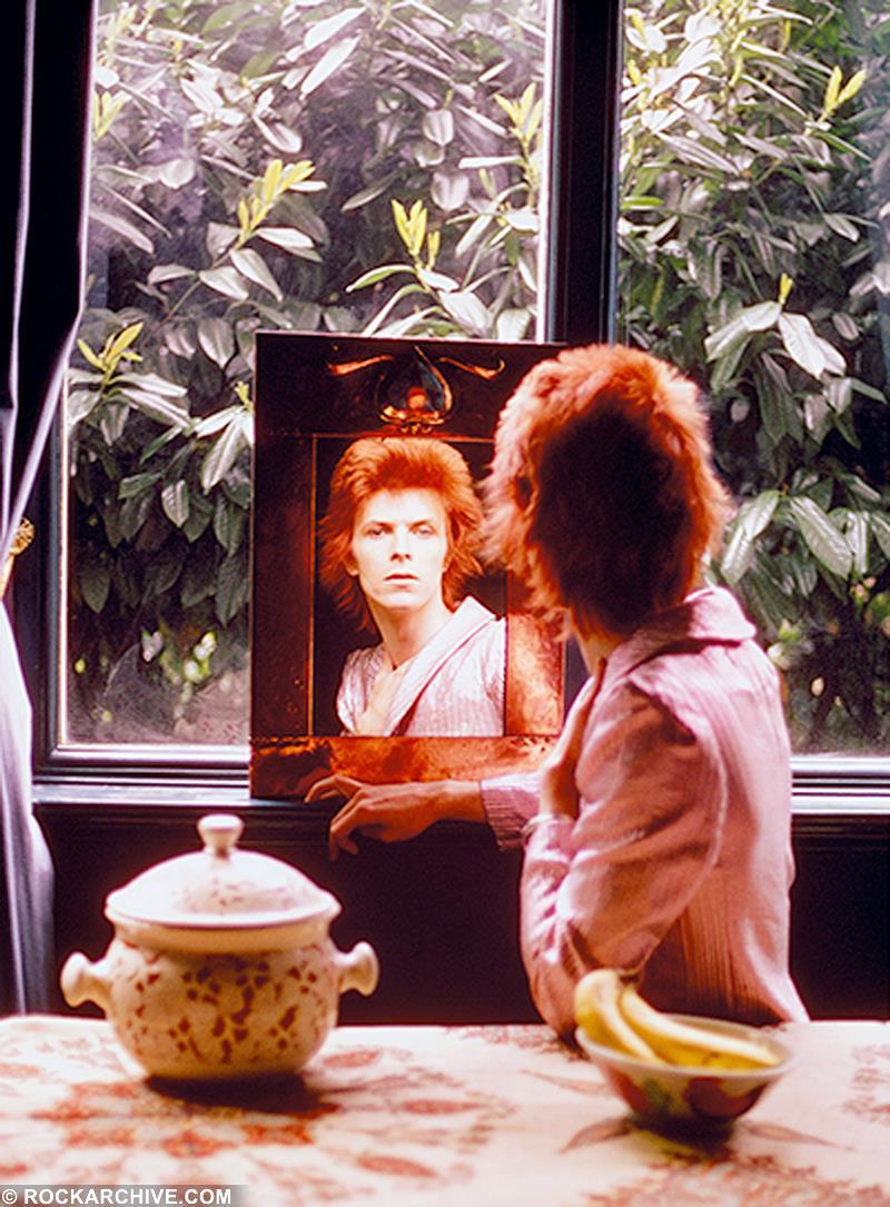 David Bowie looking into a mirror at Haddon Hall, Beckenham in March 1972 during an interview for Club International magazine. © Mick Rock