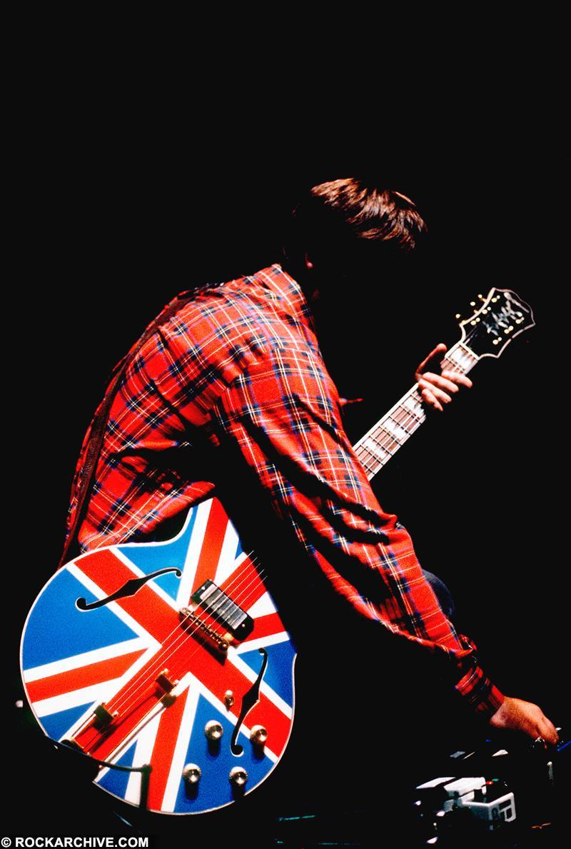 Noel Gallagher of Oasis, with his signature Union Jack guitar. © Jill Furmanovsky