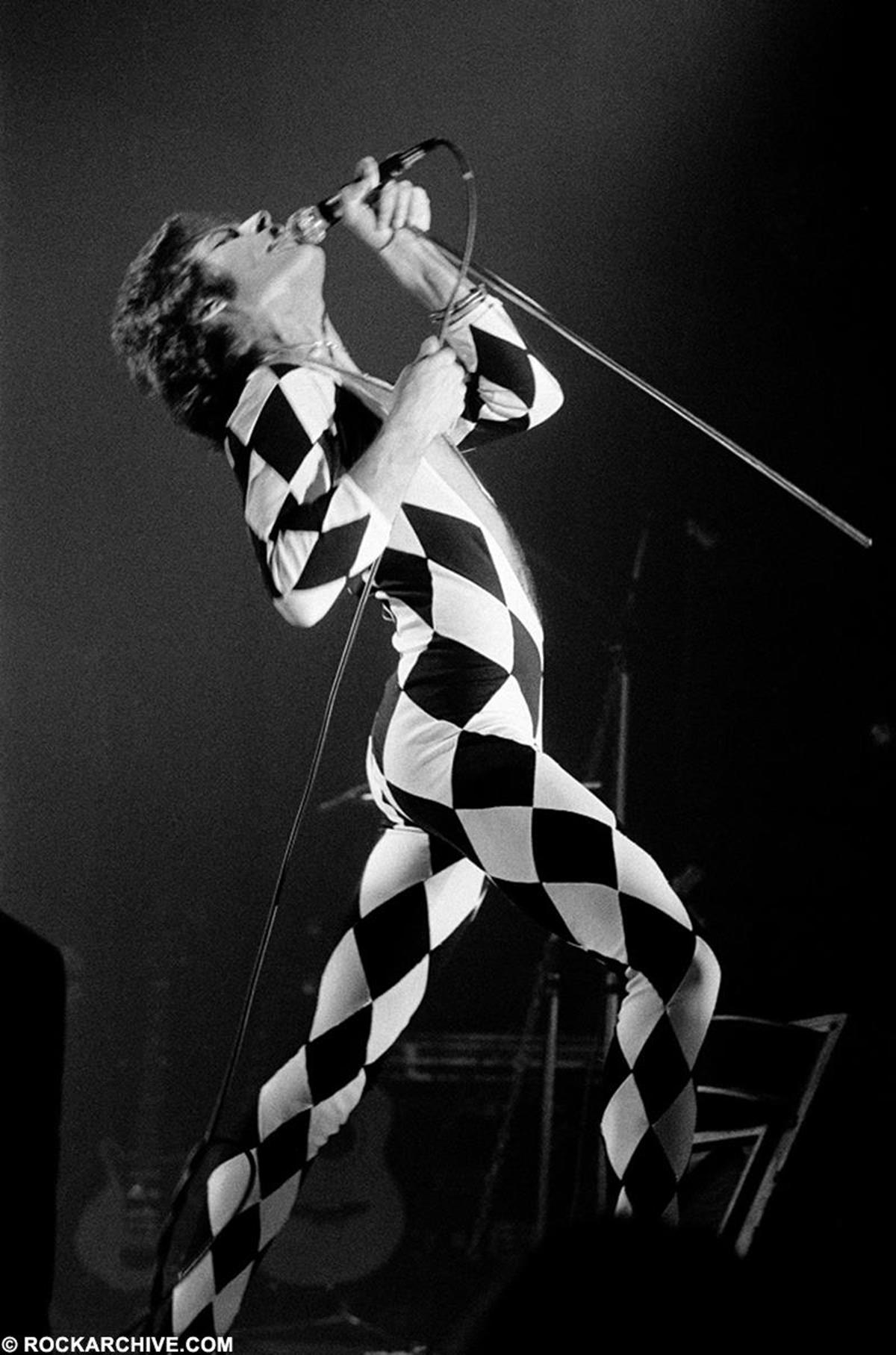 Freddie Mercury performing onstage wearing a harlequin one-piece at Brøndby Hallen, Copenhagen in May 1977. © Jorgen Angel