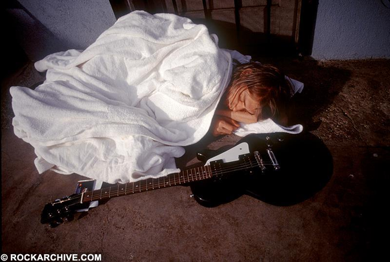 Kurt Cobain sleeping on a poolside whilst on Nirvana publicity shoot for 'Nevermind' in 1991. © Kirk Weddle