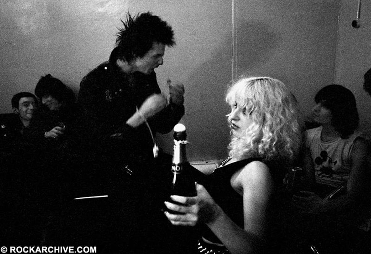 "Photographer Jill Furmanovsky recalls '""I was a little afraid of Sid and kept my distance when I saw him in clubs etc. Nevertheless I was brave enough to snatch this image of him and Nancy in the dressing room after a Ramones gig that took place on New Years' Eve, hence the bottle of champagne in Nancy's hand. In the murky background is Linda Stein who was married to Seymour Stein of Sire Records, and Dee Dee Ramone listening intently to Sid. None of those mentioned are alive now."" © Jill Furmanovsky"