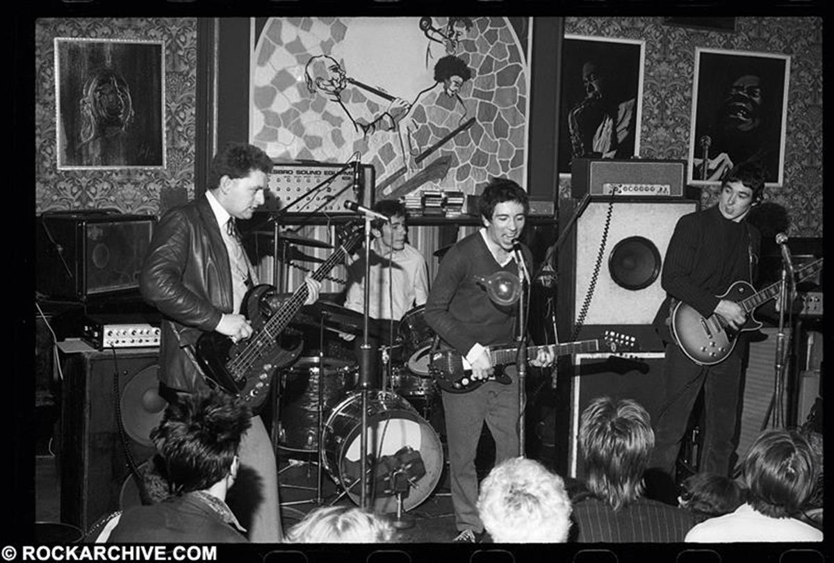 Punk group Buzzcocks performing at the legendary live music venue Band On The Wall, Manchester on 2nd May 1977. Band members were bassist Garth Smith, drummer John Maher, singer Pete Shelley and guitarist Steve Diggle. © Kevin Cummins