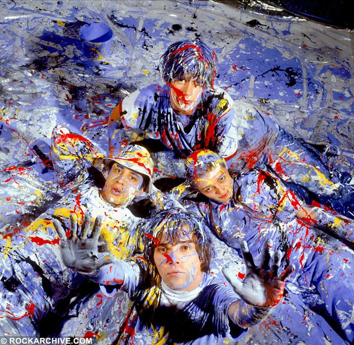 The iconic Stone Roses NME cover, taken in November 1989. Photographer Kevin Cummins says, 'I'd wanted to photograph the band (Ian Brown, John Squire, Mani and Reni) as a John Squire painting for ages. We finally set it up - they could only do it on a Sunday - in Manchester. I spent the morning turning the studio into a polythene cube - I hadn't told the owner our plan and I was worried about his studio looking like we'd played paintball for 24 hours in there. John brought the paint - we started with blue and white - for Manchester City - my team. Each time he added another colour he would paint himself then lie in the shot. After two hours without heating - lying in cold wet paint we'd got the shots. That's when I broke the news to them that there were no showers in the studio. They all had to walk through Manchester City centre dripping in multi coloured paint and go back to Ian Brown's flat to shower it off. The handprints are still down the stairwell of the building.' © Kevin Cummins