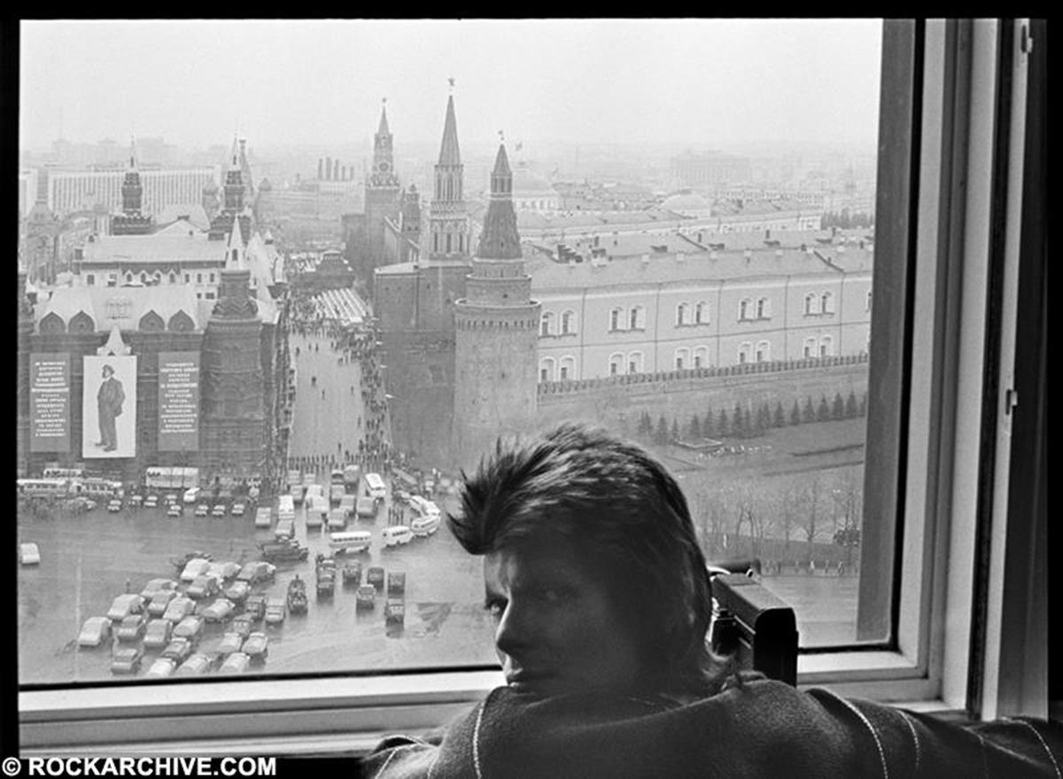 "David Bowie filming the May day Parade in Moscow in 1973. Photographer Geoff MacCormack recalls, ""We were given a list of do's and don'ts when we arrived in Siberia to board the 'Trans Siberian Express' - what we could and couldn't photograph - so David was breaking a whole stack of rules by filming the event, considering the amount of military hardware on show. That's why he's looking a little furtive."" © Geoff MacCormack"