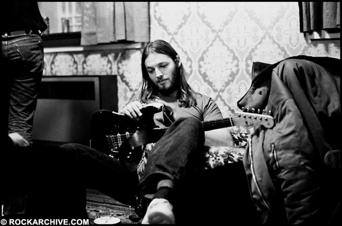 David Gilmour taking a quiet moment backstage with his legendary 'Black Strat', during the 'Dark Side of the Moon' tour in 1974. © Jill Furmanovsky